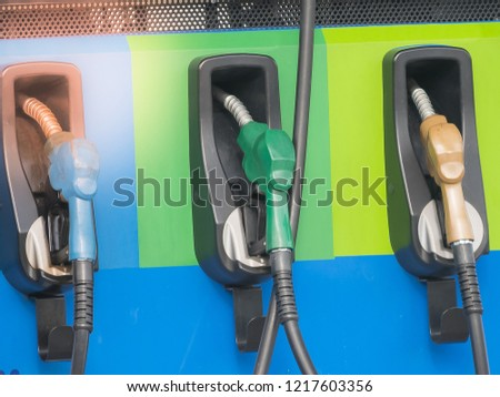 blue green orange fuel gasoline dispenser nozzles background at gas station #1217603356