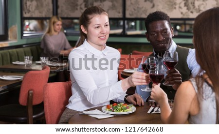 Cheerful pair with young female friend having dinner and drinking red wine at restaurant #1217642668