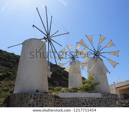 Mills on the island of Crete. White windmill on blue sky background.  #1217715454