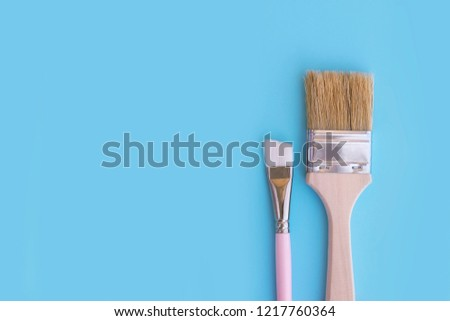 Two paint brushes on blue background. #1217760364