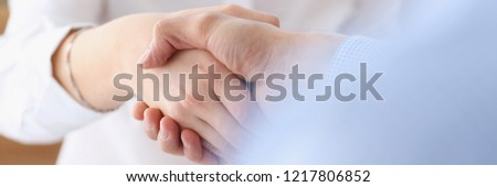 Businessman and woman shake hands as hello in office closeup. Friend welcome introduction greet or thanks gesture product advertisement partnership approval arm strike a bargain on deal concept #1217806852