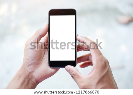 Cropped shot view of man hands holding smart phone with blank copy space screen for your text message or information content, female reading text message on cell telephone during in urban setting. #1217866870