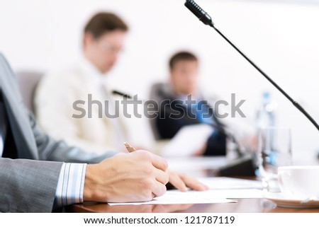 Businessman writing on paper notes, to communicate with colleagues in the background #121787119