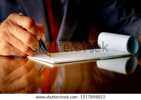 Businessman in suit cloth with necktie, hand writing and signing check book on the wooden table at modern office. Paycheck concept. Payment by cheque. Copyspace with reflection. #1217898823