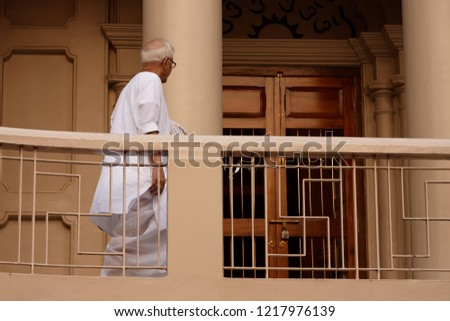 An old Indian Bengali man in Dhoti, an ethnic and traditional Bengali attire is walking towards a door near a balcony. Indian lifestyle #1217976139