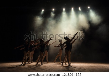Ballet class on the stage of the theater with light and smoke. Children are engaged in classical exercise on stage. #1218014122
