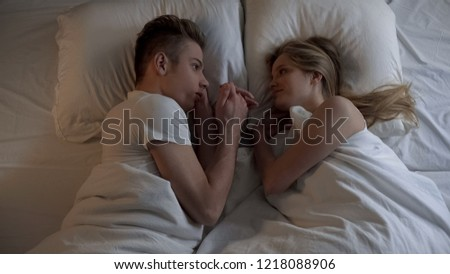 Beautiful couple lying in bed and holding hands at night time, romantic moments #1218088906