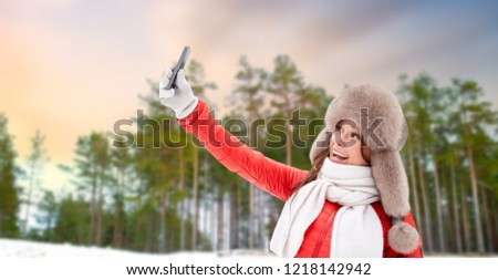people, technology and leisure concept - happy woman in fur hat taking selfie by smartphone over winter forest background