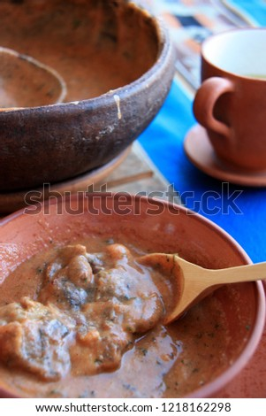 """Maize Soup with Alpaca Meat (Lomo de Alpaca), a well known delicacy in the Andes Mountain Region in Peru. Clay cup of """"Mate de Coca"""" on the right side of the picture."""