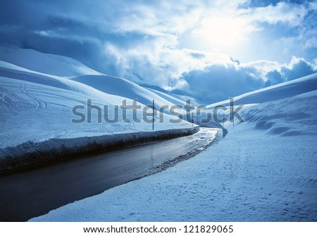 Picture of beautiful snowy highway, black clean asphalt road in mountains covered white snow, wintertime weather, blue cloudy sky, cold frosty day, Christmas vacation, landscape of driveway