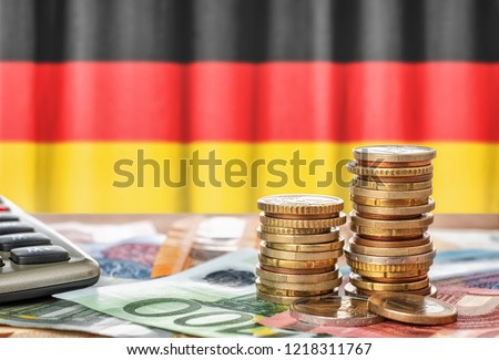 Euro banknotes and coins in front of the national flag of Germany Royalty-Free Stock Photo #1218311767