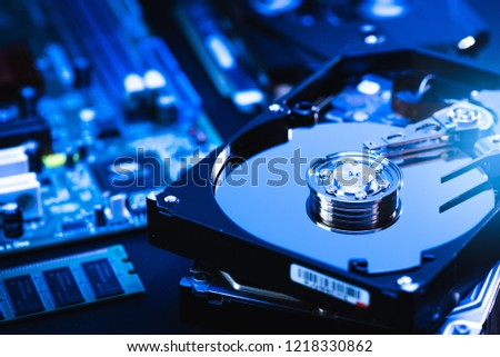 The abstract image of inside of hard disk drive on the technician's desk and a computer motherboard as a component. the concept of data, hardware, and information technology. #1218330862
