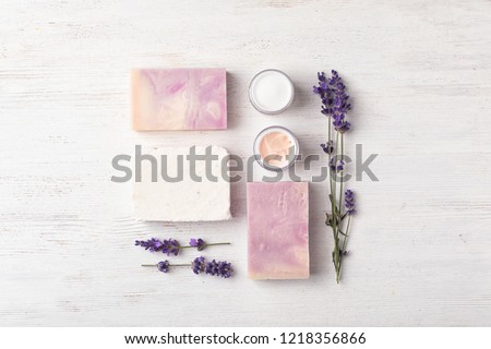 Flat lay composition with handmade soap bars and ingredients on white wooden background Royalty-Free Stock Photo #1218356866