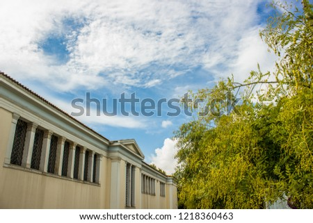 university campus long building in garden space with trees on blue sky with clouds background, copy space #1218360463