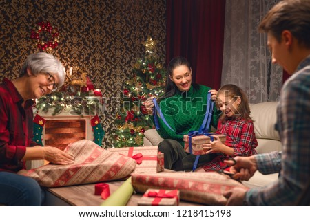 Merry Christmas and Happy New Year! Grandma, mum, dad and daughter near the tree at home. Family preparing for Holiday. #1218415498