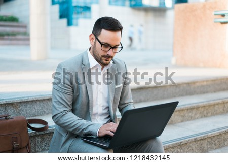 Young beautiful businessman using latop, sitting, typing a project in the city center. #1218432145