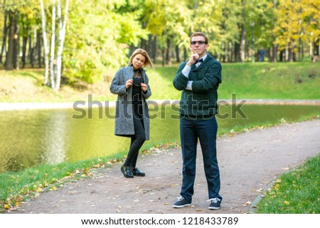 Couple talking seriously outdoors in a park with a green background #1218433789