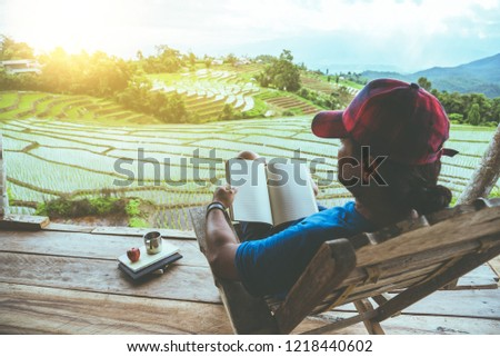 Asian man travel nature. Travel relax. sit reading book the balcony of the resort. View of the field on the Moutain in summer. Thailand #1218440602