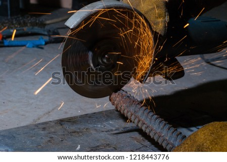 metalworking with a hand-held circular saw, close up, the disk is blurred in motion, many sparks are visible #1218443776
