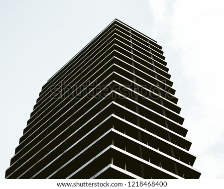 Black and white looking up shot of a tall apartment building in a white clouded sky. The structure has a symmetrical pattern.