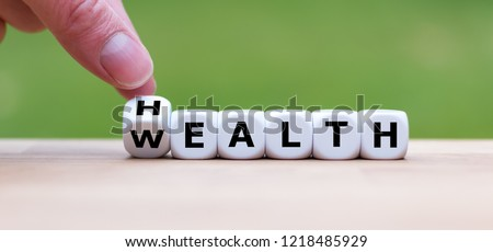 """Hand is turning a dice and changes the word """"Health"""" to """"Wealth"""" Royalty-Free Stock Photo #1218485929"""