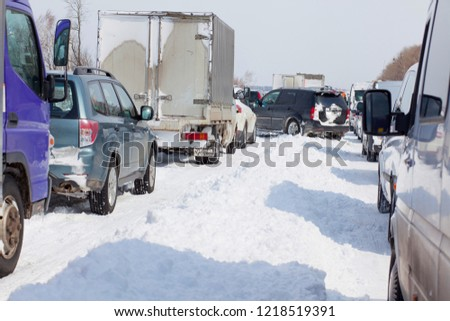 Traffic jam in winter after heavy snowfall. Cars covered in snow after a blizzard #1218519391