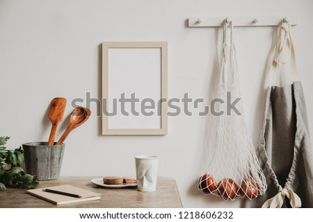Vintage and coozy kitchen interior with mock up photo frame, notebook, breakfast and kitchen accessories. Minimalistic concept of kitchen space.