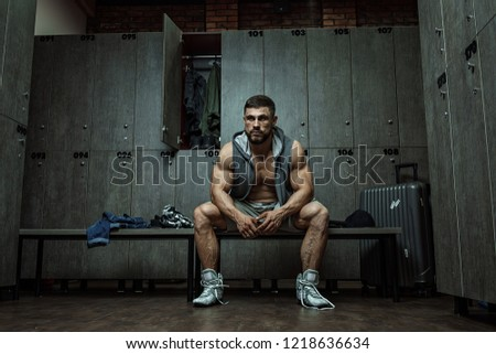 handsome muscular athletic man with a towel in the locker room after working out #1218636634