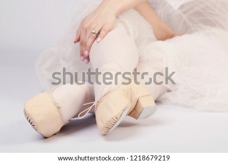 Ballerina lying down with legs crossed. Close-up image of pointe shoes for ballet. Isolated, studio shot, white background. #1218679219