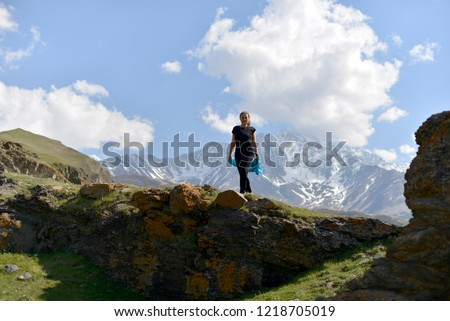 Young woman in t-shirt among snowy mountain peaks. #1218705019