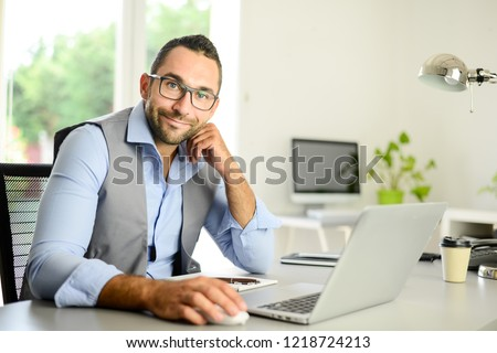 portrait of handsome trendy casual mid age business man in office desk with laptop computer  #1218724213