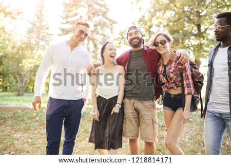 Group of multiracial friends dressed in casual summer clothing with smartphone having fun together at park, watching funny video in social media. #1218814171