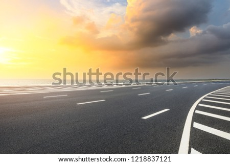 Asphalt road and dramatic sky with coastline at sunset #1218837121