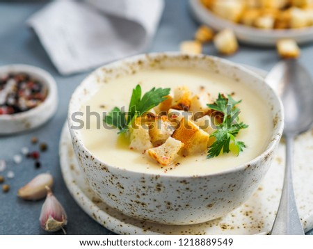 cauliflower potato soup puree on stone background,Creamy cauliflower soup with toasted bread croutons.Vegetarian healthy food concept. Ideas and recipes for winter meal.Shallow DOF.Copy space for text #1218889549