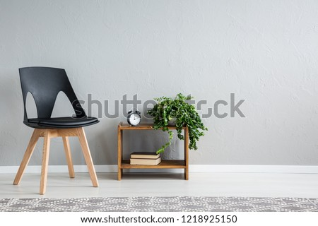 Stylish black chair next to shelf with two books, clock and green plant in pot, real photo with copy space on the wall #1218925150
