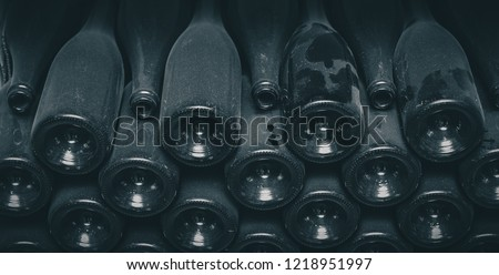 Very dusty old wine bottles stacked on each other in a wine cellar. Horizontal picture of dirty and dusty rears of wine bottles stacked together.