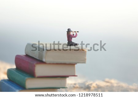 miniature woman looks at the infinity with the spyglass on a scale of books #1218978511