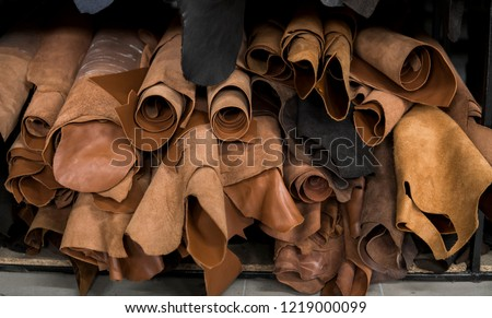 Different pieces of leather in a rolls. The pieces of the colored leathers. Rolls of natural brown red leather. Raw materials for manufacture of bags, shoes, clothing and accessories. #1219000099