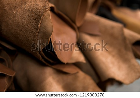Different pieces of leather in a rolls. The pieces of the colored leathers. Rolls of natural brown red leather. Raw materials for manufacture of bags, shoes, clothing and accessories. #1219000270