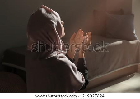 Young Muslim woman praying at home #1219027624
