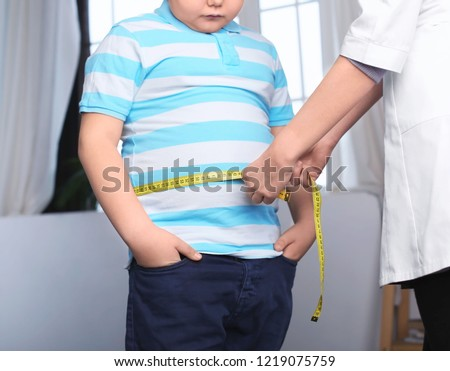 Doctor measuring overweight boy in clinic #1219075759