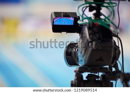 Modern camera during reporting from swimming basin, shallow dof. #1219089514