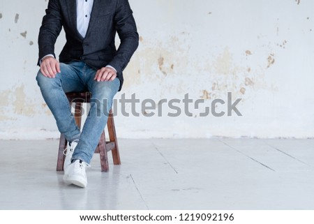 man in jacket and jeans sitting on a chair. confident business trainer or entrepreneur. smart casual dress code. #1219092196