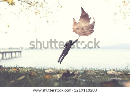 surreal autumn, man flying away with a big leaf