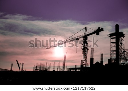 A construction crane and behind it is a sunset in purple sky. #1219119622