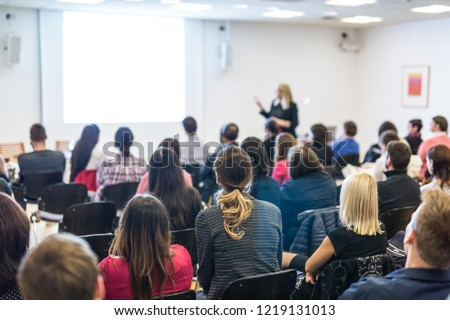 Business and entrepreneurship symposium. Female speaker giving a talk at business meeting. Audience in conference hall. Rear view of unrecognized participant in audience. Copy space on whitescreen. #1219131013