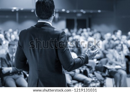 Speaker giving a talk on corporate business conference. Unrecognizable people in audience at conference hall. Business and Entrepreneurship event. Black and white image. #1219131031
