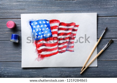 Watercolor painting of American national flag with brushes on wooden table