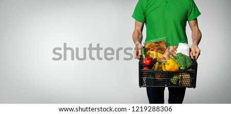 food delivery service - man with groceries box on gray background with copy space Royalty-Free Stock Photo #1219288306