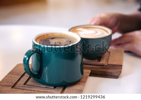 Close up image of a hand holding a green coffee mugs in cafe #1219299436